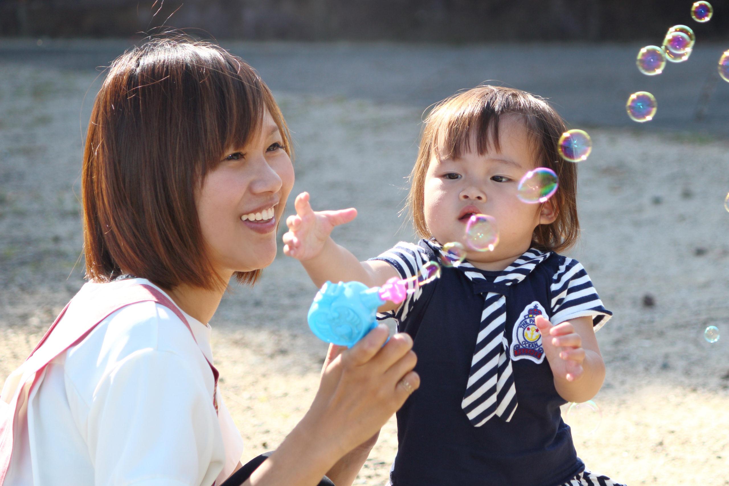 シャボン玉で遊ぶ保育士と子供