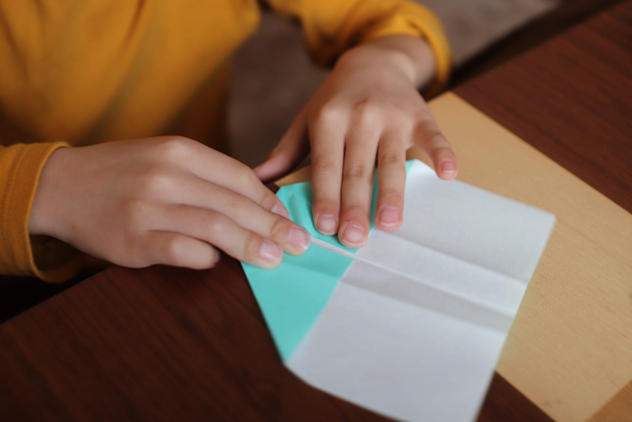折り紙を折る子供