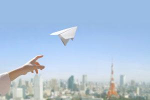 空に紙飛行機を飛ばす